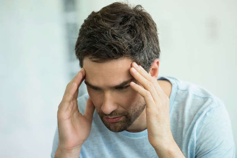 a man talking on a cell phone: Man holding head