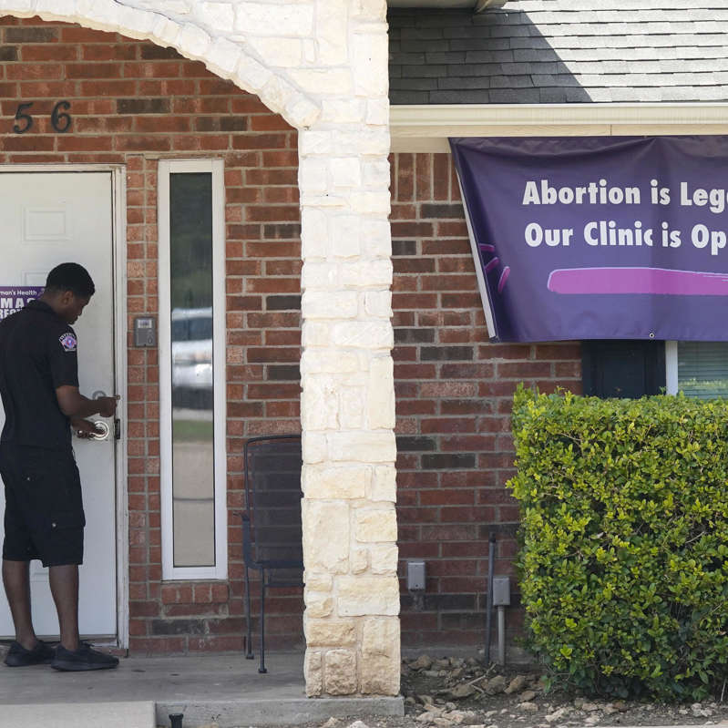 a man standing in front of a brick building: Supreme Court-Abortion