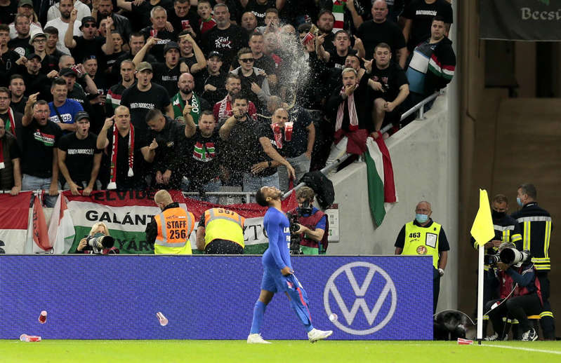 a group of people jumping in front of a crowd: England's Raheem Sterling is abused by Hungary fans after opening the scoring (Attila Trenka/PA). - PA Wire