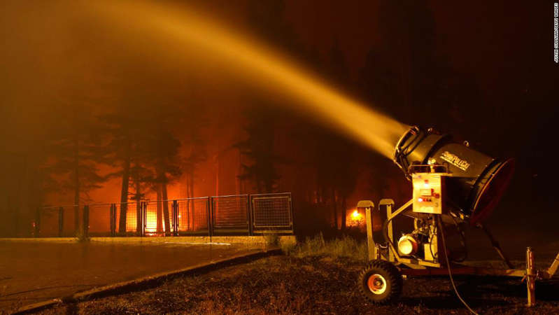 a rainbow over a city at night: A snow machine blows water on a structure at Sierra-at Tahoe ski resort as the Caldor Fire moves through the area on August 30, 2021 in Twin Bridges, California.