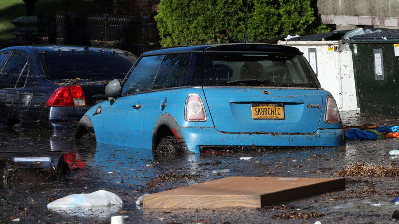 a blue car parked in a parking lot: Local residents escape flooding in Mamaroneck, New York