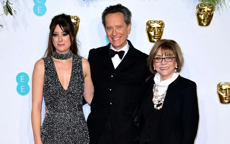 Richard E. Grant et al. posing for the camera: Richard E. Grant attending the 72nd British Academy Film Awards with his wife Joan and daughter Olivia - Ian West/PA