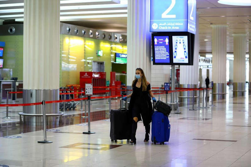 a person standing next to a bag of luggage: Dubai travel: Emirates suspends Nigeria flights until September 19
