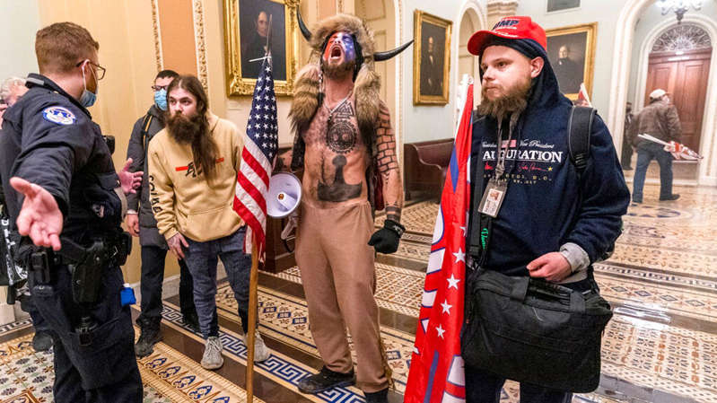a group of people standing in front of a crowd: Chansley has referred to himself as the 'QAnon Shaman'. Pic: AP