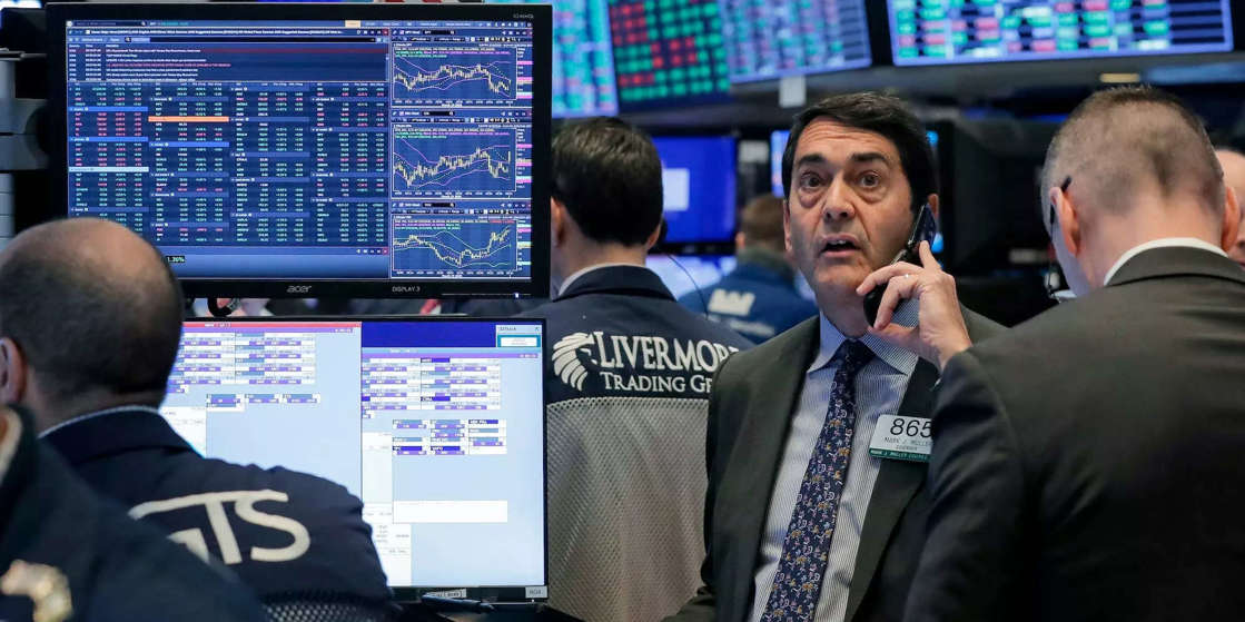 a man standing in front of a computer: US stocks fall after massive miss on August jobs report