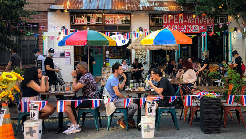 Diners eat al fresco due to COVID-19 concerns in the West Village, Friday, June 26, 2020, in New York. New York City Mayor Bill de Blasio says he's delaying the planned resumption of indoor dining at restaurants in the city out of fear it would ignite a spike in coronavirus infections. (AP Photo/John Minchillo)