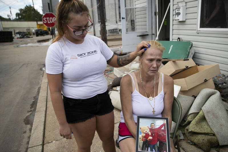 a woman sitting on a sidewalk: Laura Sinnott Caroluzzi tears up while she holds a photo of her husband, Jack Caroluzzi, and is comforted by Lauren Caroluzzi, Jack's daughter.