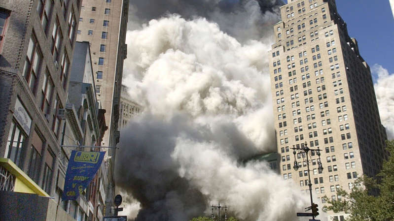 a city with smoke coming out of it: People flee the falling South Tower of the World Trade Center on Tuesday, September 11, 2001. Pic: AP