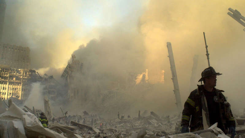 a man with smoke coming out of it: A lone firefighter moves through piles of debris at the site of the World Trade Center in the aftermath of the attack. Pic: AP