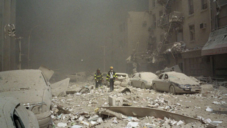 a pile of dirt: Firemen walk through a dust and debris-covered street in lower Manhattan. Pic: AP