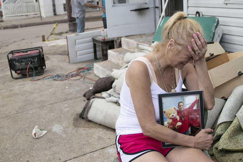 a woman holding a baby: Laura Sinnott Caroluzzi tears up while she holds a photo of her husband, Jack Caroluzzi, who died in Wednesday evening's flooding, outside of their home in Bridgeport, Pa.