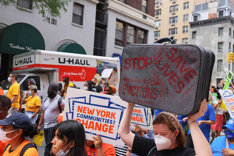 a group of people on a city street: People march toward the New York City office of Gov. Kathy Hochul calling for a stop to evictions on August 31, 2021 in New York City.