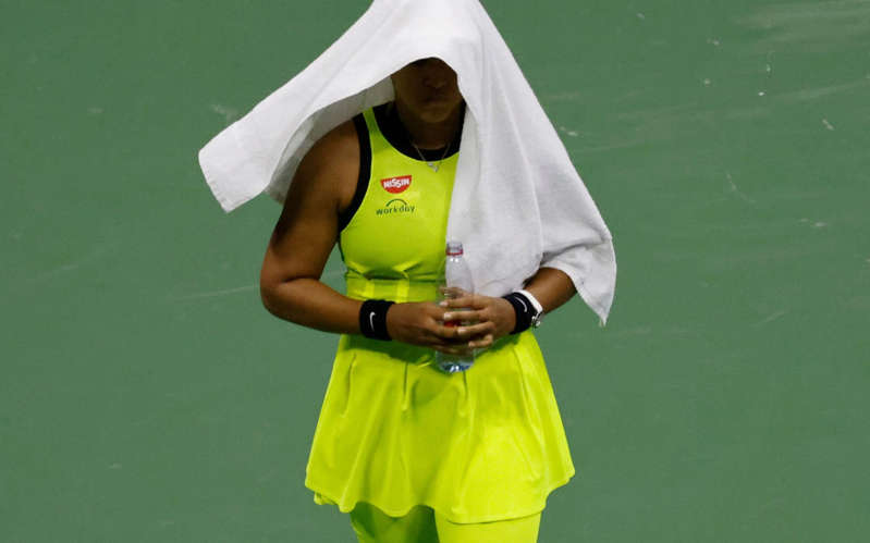a hand holding a green ball on a court with a racket: Osaka's future looks uncertain after an unusually emotional performance - EPA