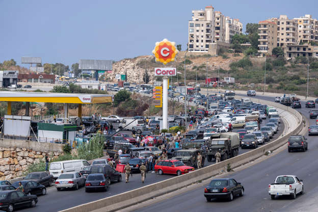 a car driving on a city street filled with lots of traffic: A crowded petrol station on the main road that links Beirut to south Lebanon. AP
