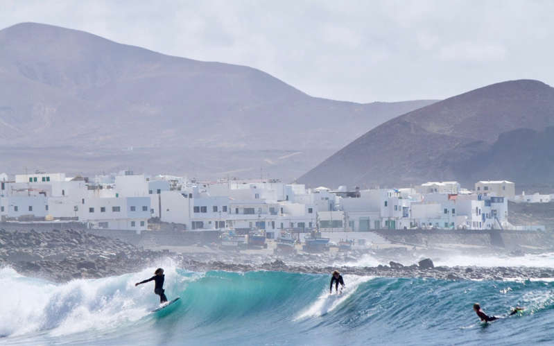 a man riding a wave on a surfboard in the water: surfing lanzarote - iStock