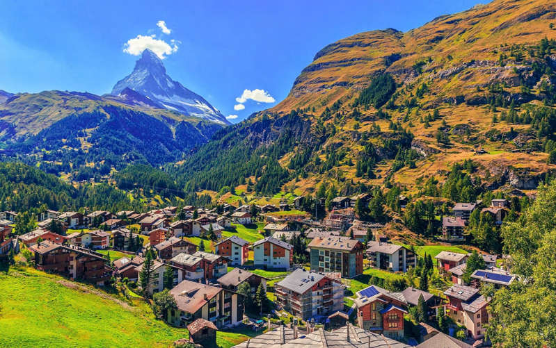a group of people in a field with a mountain in the background: zermatt - Getty