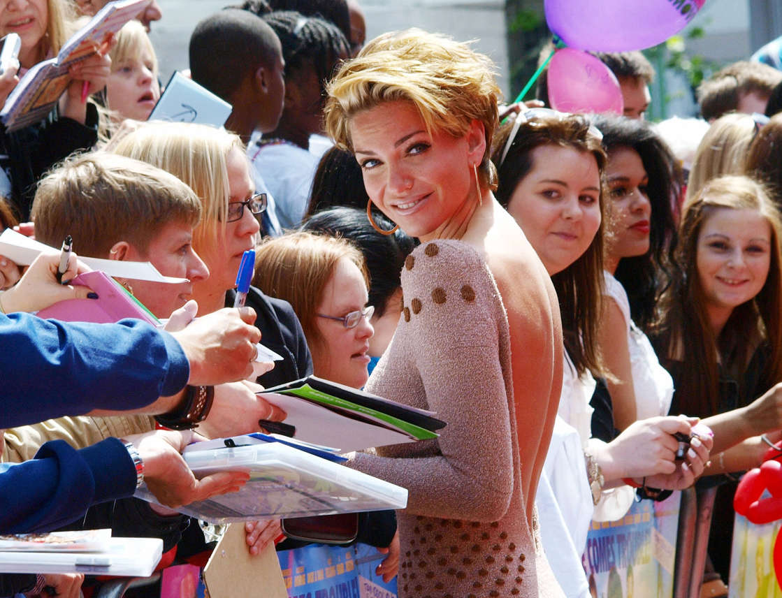 a group of people standing in front of a crowd: Sarah Harding from the group 'Girls Aloud' meets with fans as she arrives at the premiere of the film,' Horrid Henry', in central London on July 24, 2011. (Max Nash / AFP - Getty Images)