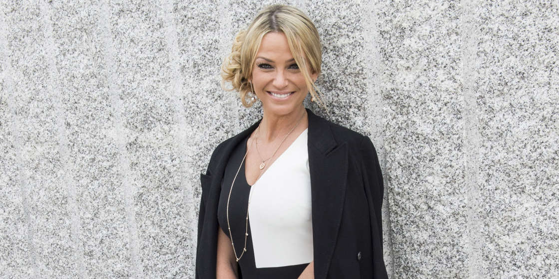 Sarah Harding wearing a suit and tie smiling at the camera