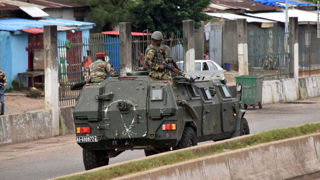 a truck is parked on the side of a road: Members of Guinea's armed forces drive through the central neighborhood of Kaloum, in Conakry, on September 5.
