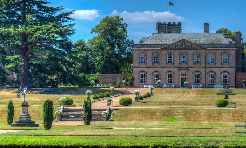 a path with trees on the side of a building: 'There are some lovely walks in the grounds of 18th-century Melbourne Hall': Melbourne, South Derbyshire.