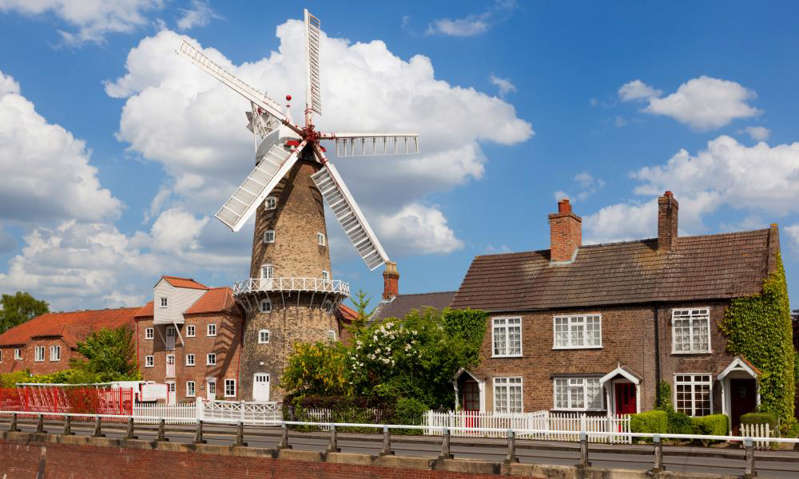 a windmill in front of a house: The Maud Foster Windmill, Skirbeck, Boston, 80ft tall to the cap ball and still in operation: Skirbeck, Boston, Lincolnshire. Photograph: Robert Harding/Alamy