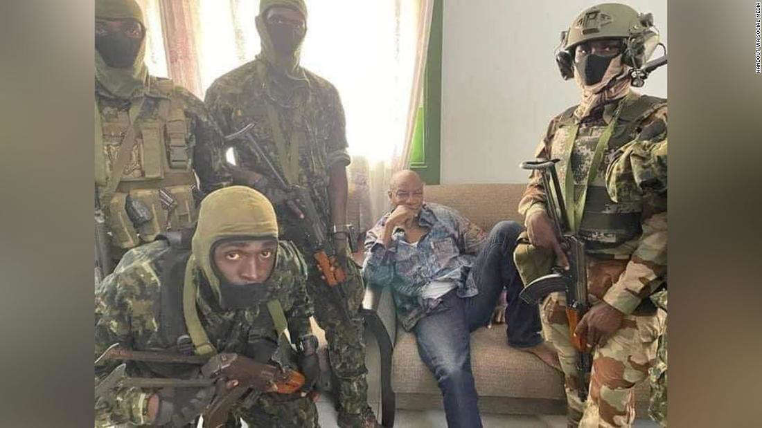 a person in a military uniform: A social media image appears to show President Alpha Conde surrounded by soldiers.