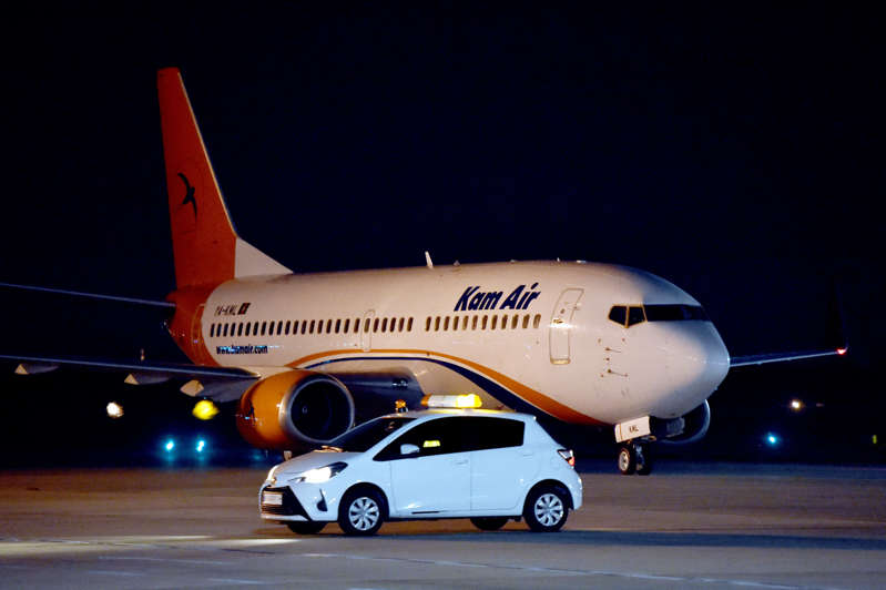 a large passenger jet sitting on top of a runway: A Boeing 737-31S Kam Air passenger plane with people evacuated from Afghanistan on board, lands at Boryspil International Airport outside Kiev, on August 23, 2021.