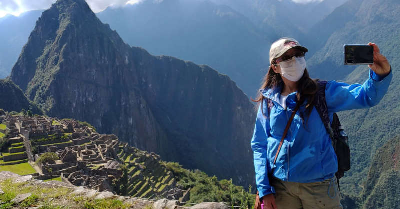 a man standing in front of a mountain: Visitors to Machu Picchu must wear masks at all times, even while taking photos.
