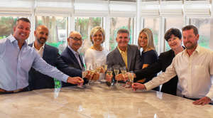 a group of people standing around a table: The Schemmel Group, which specializes on luxury waterfront properties, and the Soda Group, which also specializes in luxury properties, have combined into the Schemmel Soda Group.