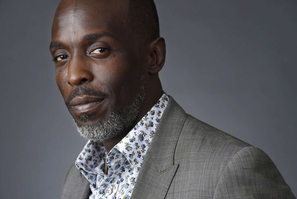 Michael K. Williams wearing a suit and tie looking at the camera