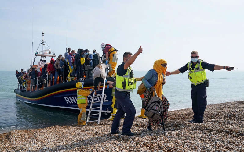a group of people that are standing in the water: Migrants are led ashore at Dungeness in Kent - Gareth Fuller/PA Wire