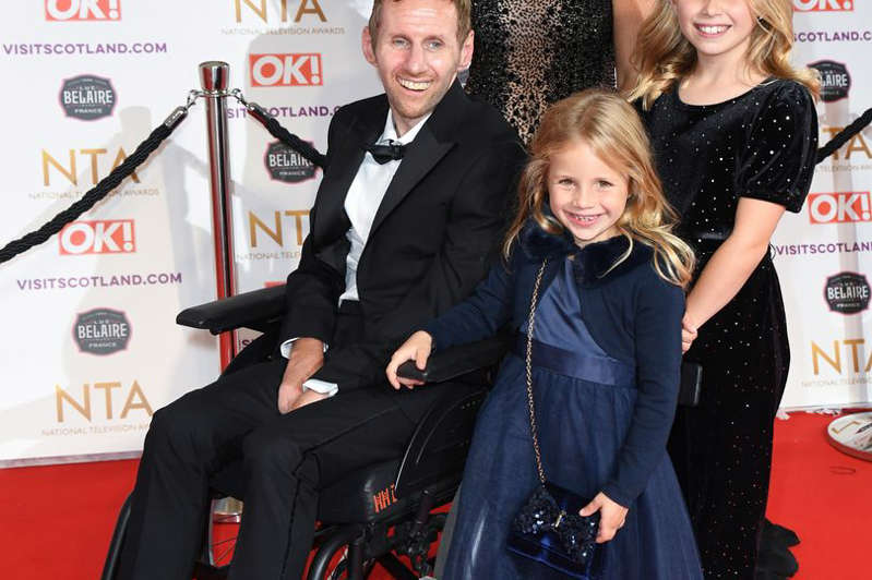 Rob Burrow et al. posing for the camera: Rob Burrow with his wife and family arriving at the National Television Awards 2021