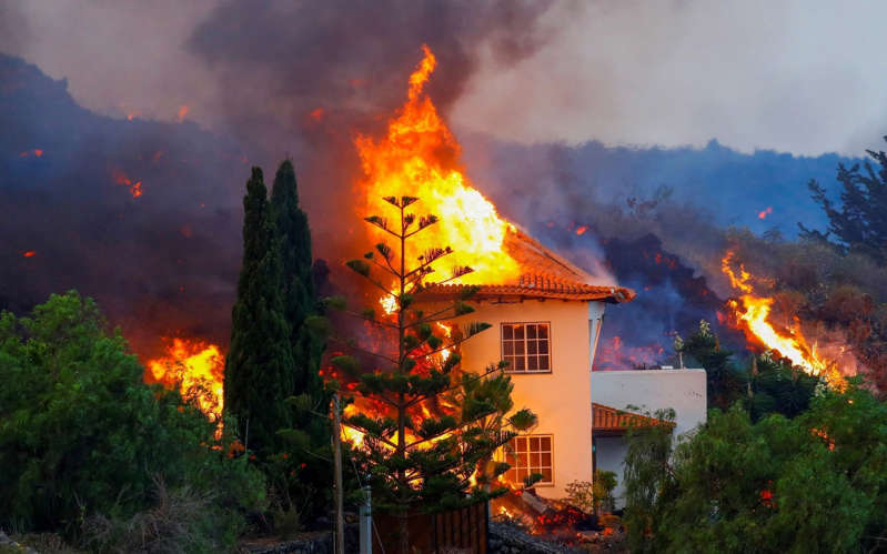 a sunset over a fire: A house burns due to lava from the eruption of a volcano - Borja Suarez/REUTERS