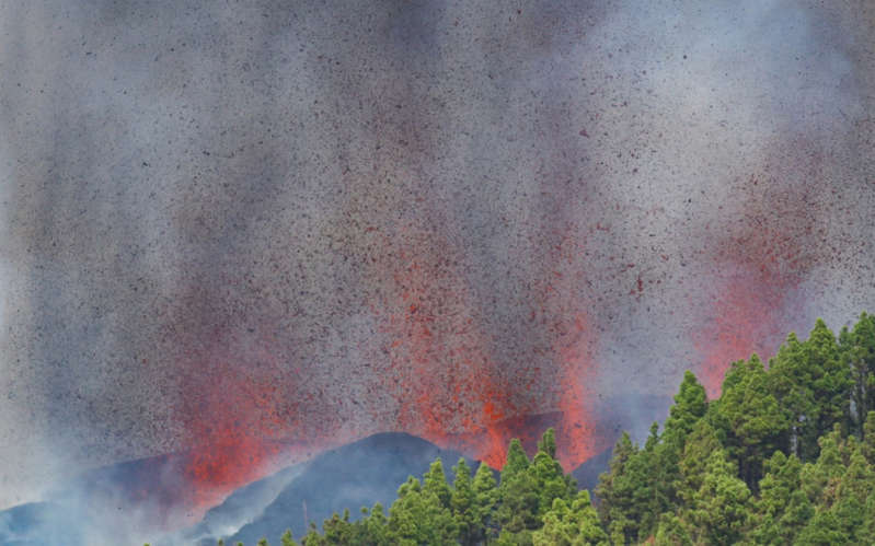 a close up of a fire: Lava and smoke rise following the eruption of a volcano in the Cumbre Vieja national park - Borja Suarez/REUTERS