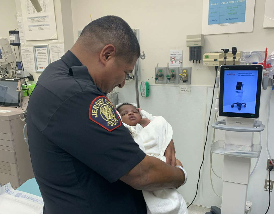 a man standing in a room: A Jersey City police officer caught a newborn baby who was tossed off a balcony.