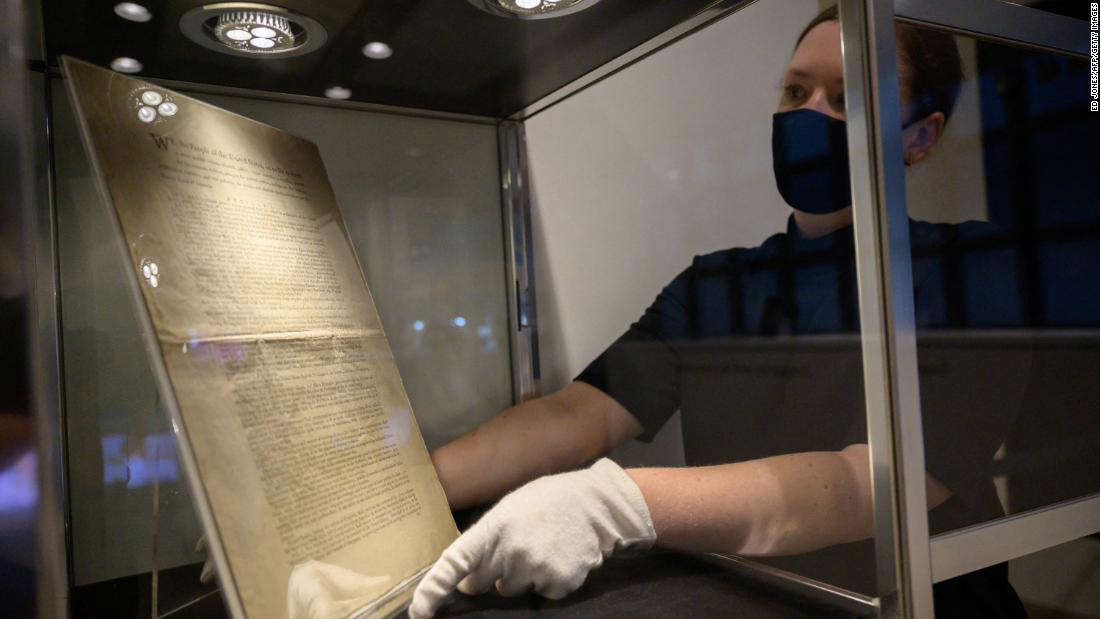 a person sitting in a room: A Sotheby's expert presents a page of the first printing of the United States Constitution, set to go on sale this November.