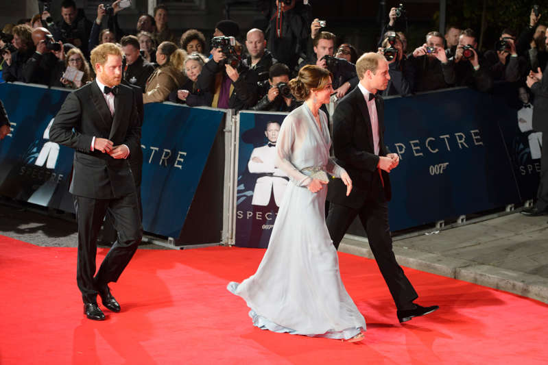 a group of people standing in front of a crowd: The Duke and Duchess of Cambridge with Prince Harry attending the world premiere of Spectre in 2015 (Matt Crossick/PA) (PA Archive)