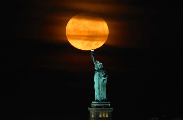 A Harvest Moon sets behind the Statue of Liberty before sunrise on September 20, 2021 in New York City.