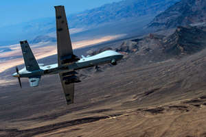 a plane sitting on top of a mountain: An MQ- Reaper piloted aircraft performs aerial maneuvers over Creech Air Force Base, Nevada, in 2015.