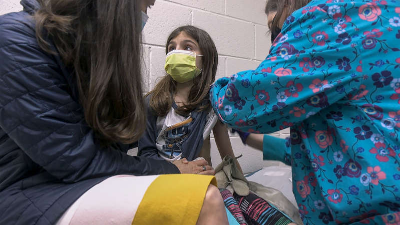 a woman sitting on a bed: Alejandra Gerardo, 9, looks up to her mom, Dr. Susanna Naggie, as she gets the first of two Pfizer COVID-19 vaccinations during a clinical trial for children at Duke Health in Durham, N.C.