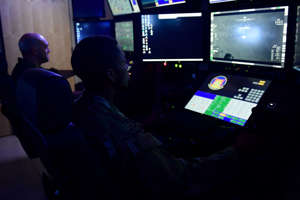 a man sitting in front of a television screen: Remotely Piloted Aircraft aircrew fly simulated missions in an MQ-9 Reaper cockpit at Creech Air Force Base, Nevada, Sept. 4, 2019.