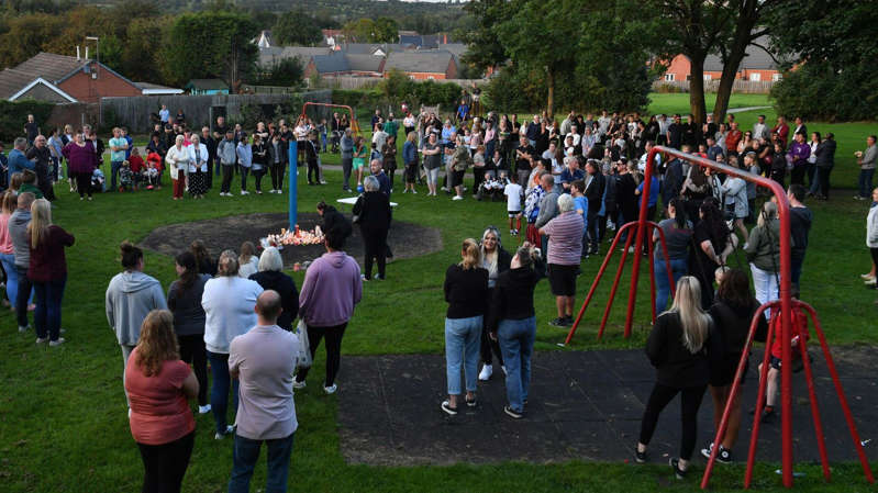 a crowd of people at a park: A vigil was held in a nearby park on Monday evening
