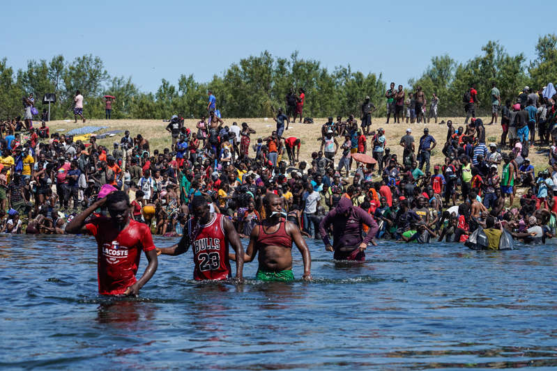 a group of people swimming in the water: Haitian migrants, part of a group of over 10,000 people staying in an encampment on the U.S. side of the border, cross the Rio Grande river to get food and water in Mexico, after another crossing point was closed near the Acuna Del Rio International Bridge in Del Rio, Texas on Sunday, Sept. 19, 2021.