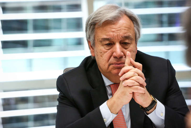 Antonio Guterres wearing a suit and tie talking on a cell phone: United Nations Secretary-General Antonio Guterres Interview
