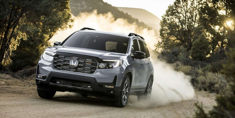 a car driving down a dirt road: All Passports receive a fresh face and more standard safety tech, while the TrailSport prepares the crossover for off-road duties. Honda's also showing a Rugged Roads Project one-off.