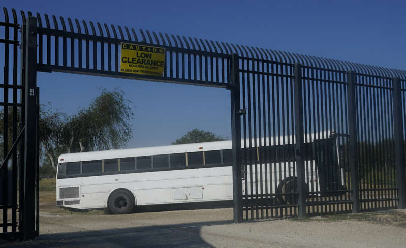 a bus parked in front of a fence