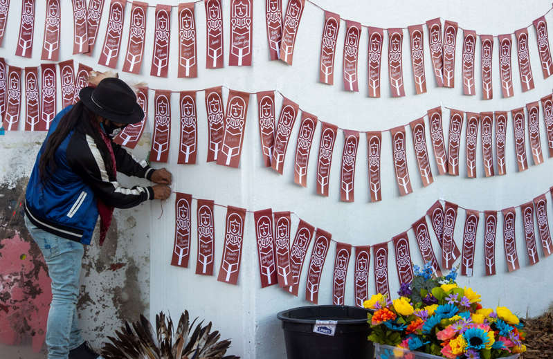 a group of people wearing costumes: (Rick Egan   The Salt Lake Tribune)  Carl Moore arranges names of murdered and missing Indigenous women and girlsvat the Indigenous Peoples Day celebration on Monday, Oct. 12, 2020.