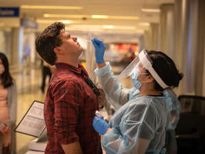a group of people standing in a room: A health care worker tests a traveller at a COVID-19 testing station at LAX airport. Allen J. Schaben / Los Angeles Times via Getty Images