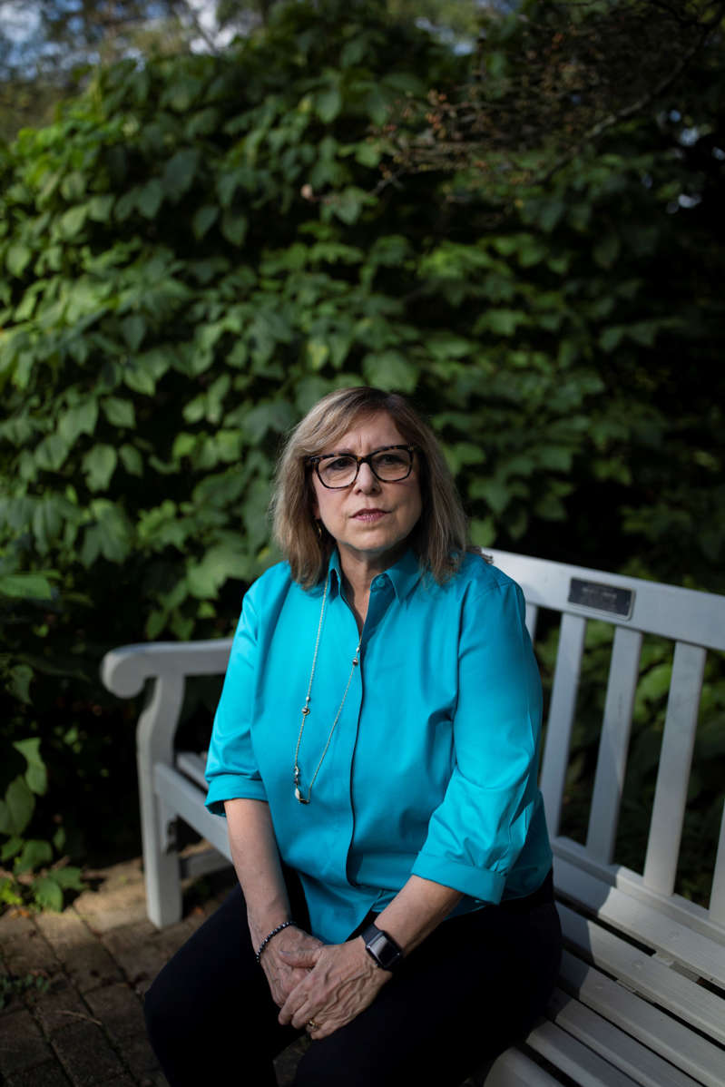 a woman sitting on a bench: Kerrie Krutchik poses for a portrait in the Park of Roses in Columbus, Ohio on Sept. 19. Krutchik had to get her face scanned by facial recognition software while working in her home office for a two-week, 8 hour-a-day contract and says she'll never do it again.