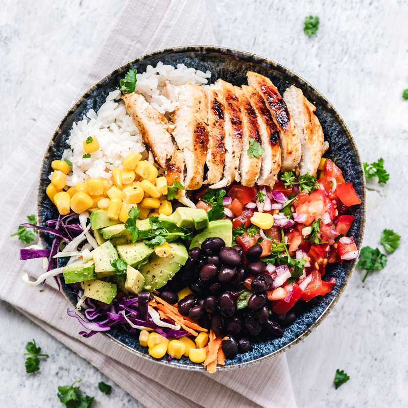 a plate of food with broccoli: Grilled chicken and rice salad bowl